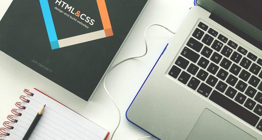 Un ordenador, una libreta y un libro sobre las tendencias en diseño web