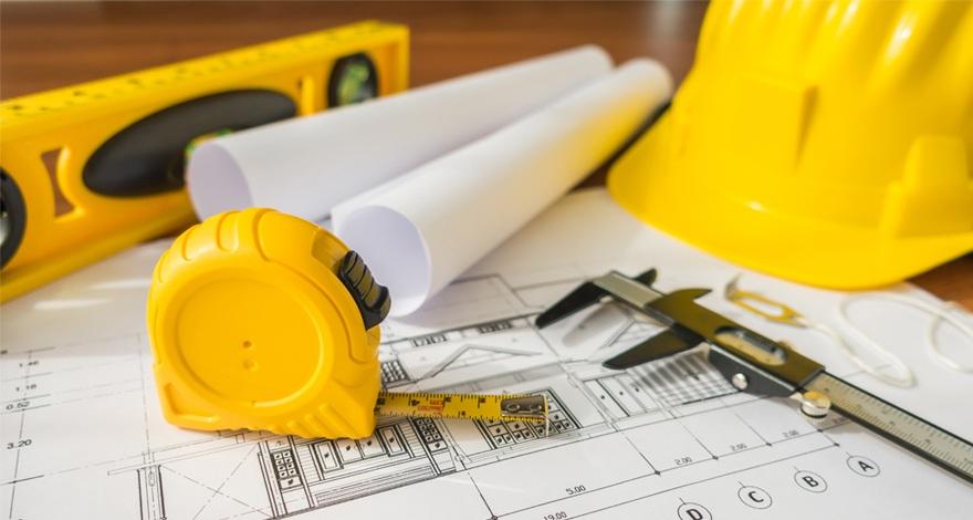 Una mesa de trabajo con un casco de obra, planos, metro y nivel