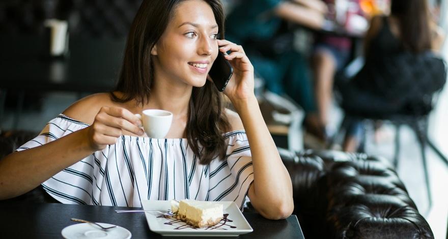 Una mujer en un restaurante tomando un café