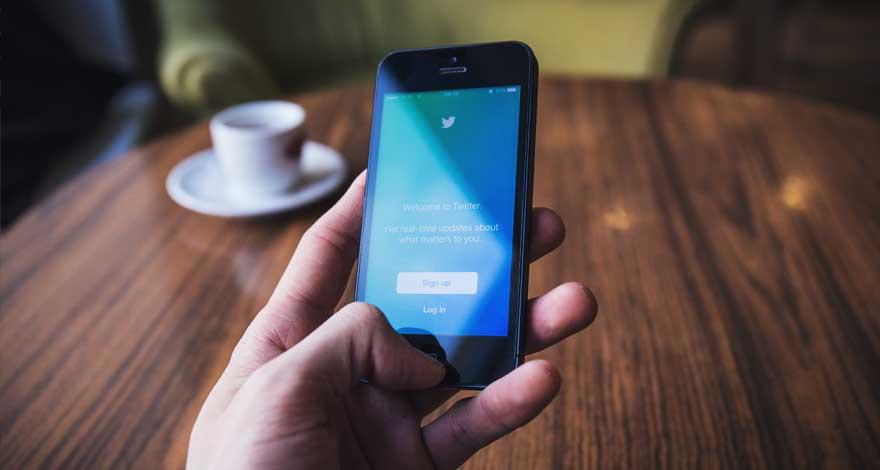 Mano sosteniendo un móvil con la pantalla de inicio de Twitter