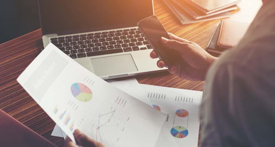 Persona sosteniendo un documento con gráficos y su teléfono en su área de trabajo de servicios de marketing