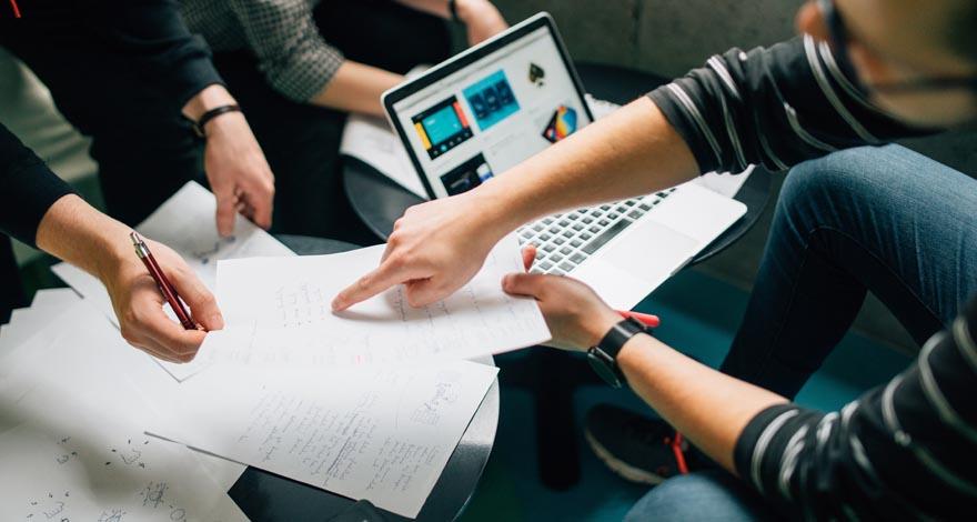 Dos personas trabajando en planes de marketing digital internacional con sus documentos y ordenadores