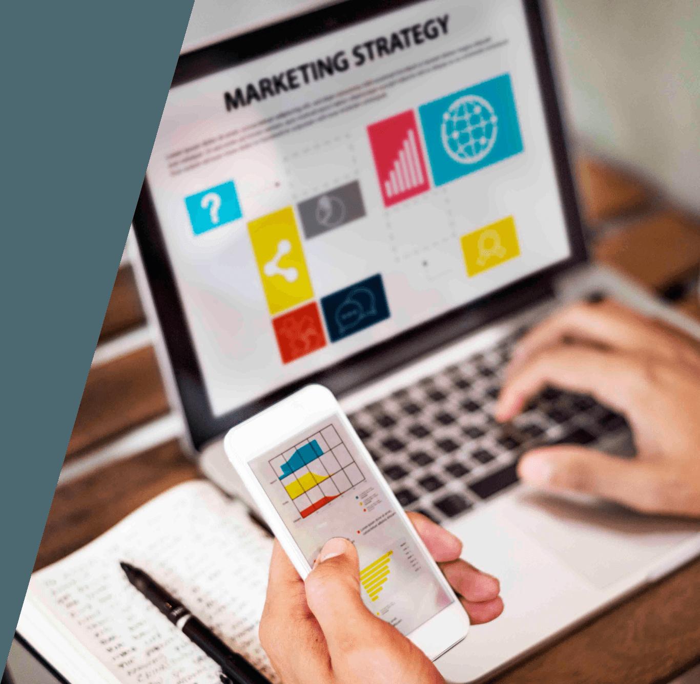 Persona con portátil y móvil analizando resultados del marketing digital