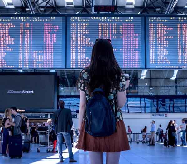 Una joven de espaldas mirando en la pantalla de una terminal todos los vuelos