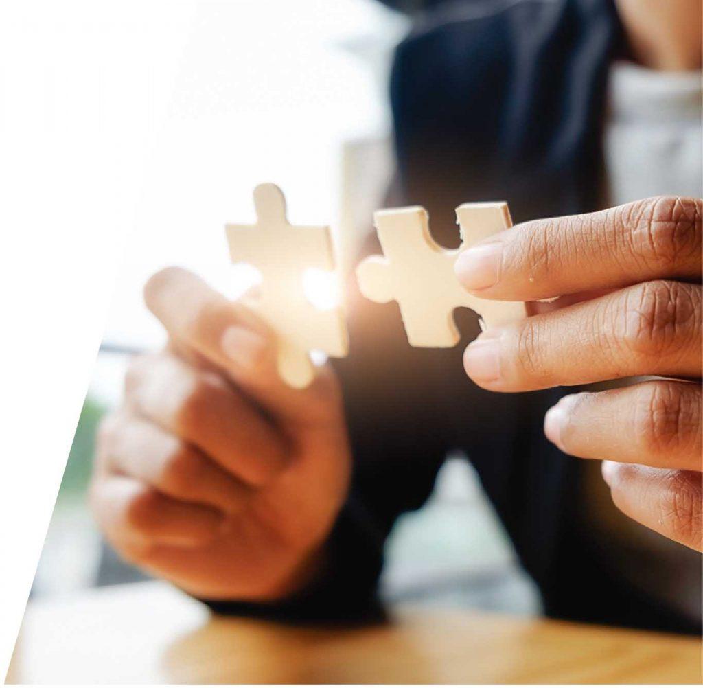 Persona uniendo dos piezas de un puzle