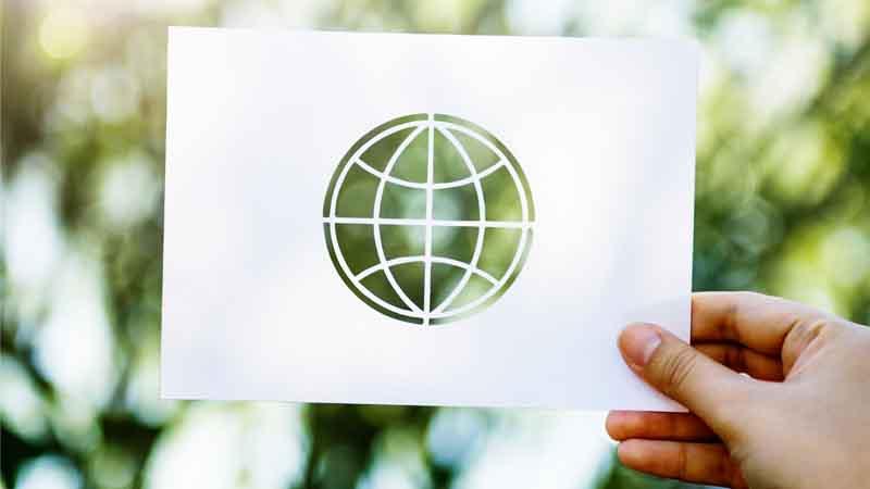 Mano sosteniendo un dibujo de un icono del mundo sobre un fondo de hojas