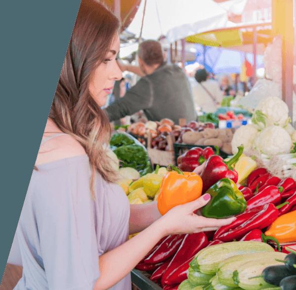 Una mujer en un mercado con tres pimientos en las manos