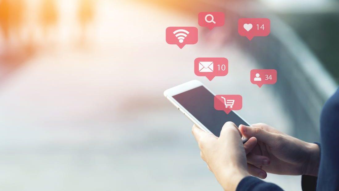 Persona sosteniendo un móvil del que salen iconos de me gusta, SMS, Wi-fi y compras