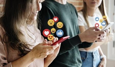 Tres jóvenes con sus móviles, de las pantallas de estos salen iconos de Facebook