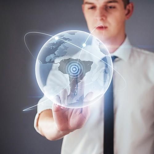 Hombre tocando un holograma que representa el mundo