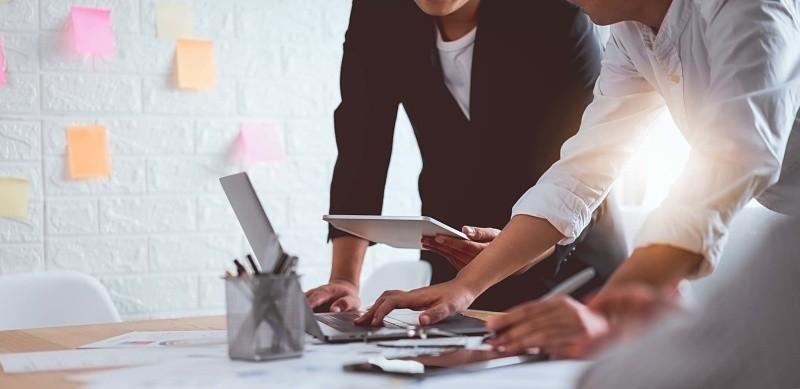 Dos personas trabajando con un portátil y tablet sobre un escritorio